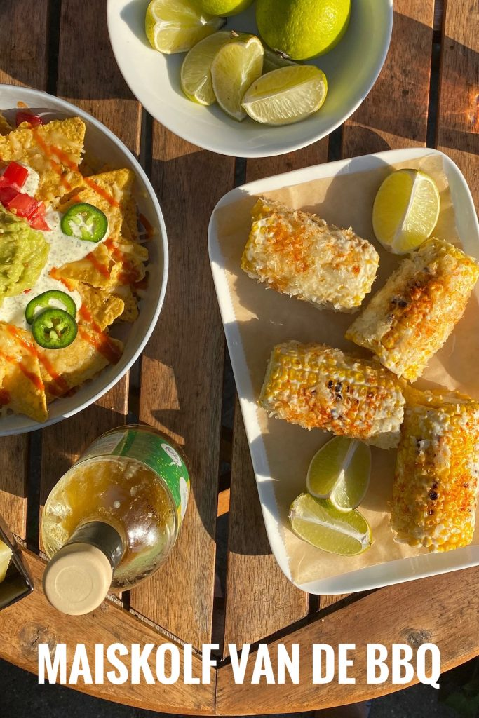mexican corn elote on table with nachos and limes